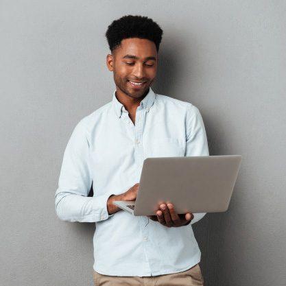 young-smiling-african-man-standing-using-laptop_171337-12867-circle